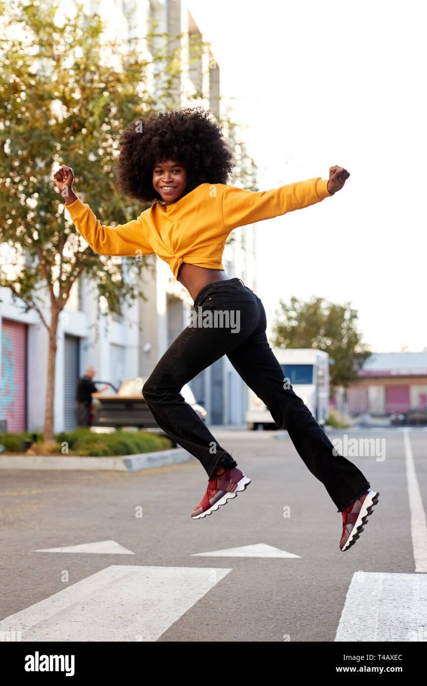 Junge schwarze Frau mit Afro Sprünge, zu Kamera suchen, beim Überqueren der Straße, Seitenansicht, vertikal Stockfoto