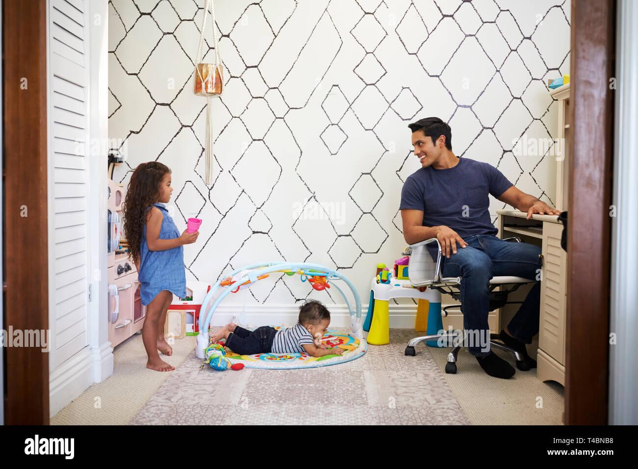Vati am Schreibtisch zu Hause arbeitet, dreht sich um, um zu seinen jungen Kinder zu sprechen, spielen in den Raum hinter ihm Stockfoto
