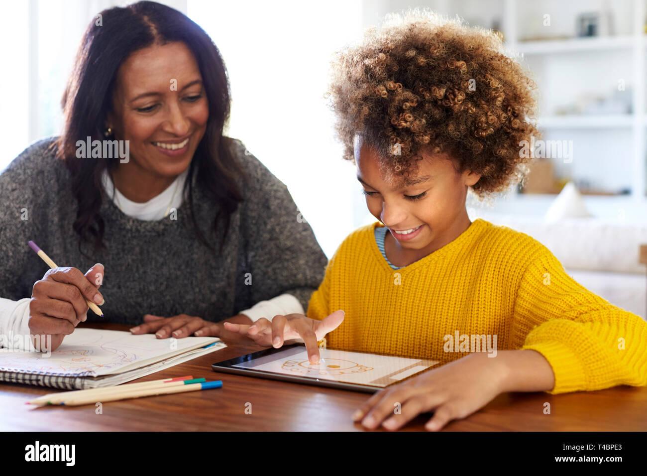 Gemischten Rennen junge Großmutter an den Tisch sitzen Hausaufgaben mit ihrer Enkelin über einen Tablet-PC, in der Nähe Stockfoto