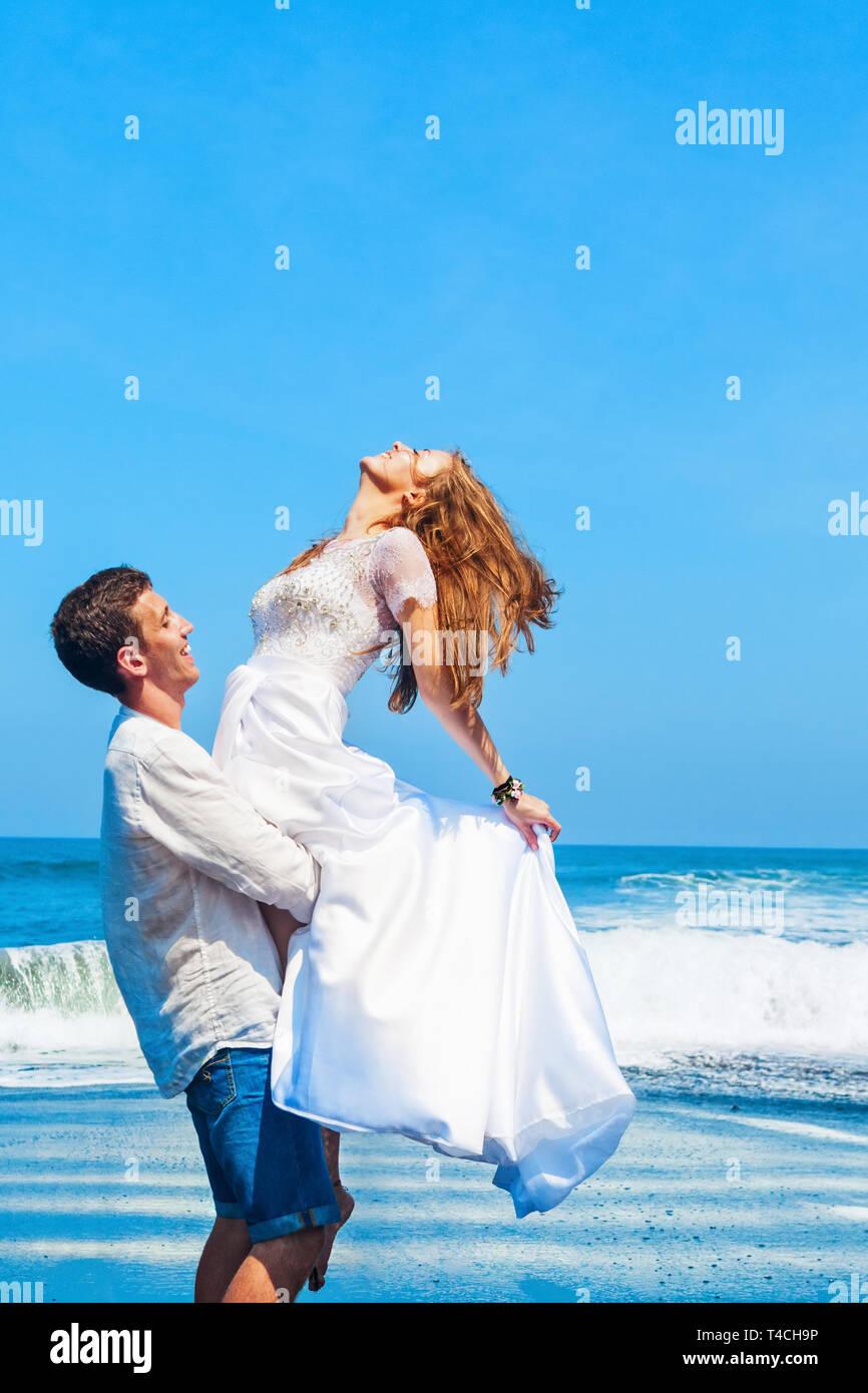 Happy Family auf Hochzeitsreise holiday - Just married junger Mann und Frau viel Spaß auf schwarzem Sand Strand. Aktiver Lebensstil, Menschen Aktivität im Freien im Sommer Stockfoto
