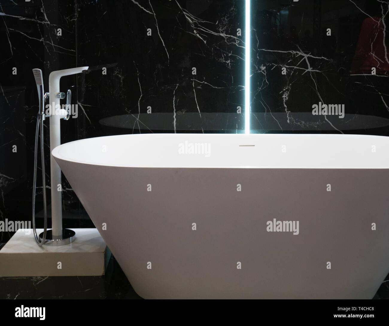 Moderne, weiße Wanne im Hotel Apartment mit schwarzem Marmor ...