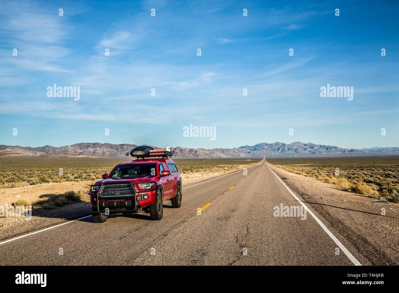 Roten Pickup Truck mit overlanding und Campingausrüstung geladen. Das Fahrzeug fährt auf der Extraterrestrial Highway in der Nähe von Area 51 in der weit geöffneten Beim Stockfoto