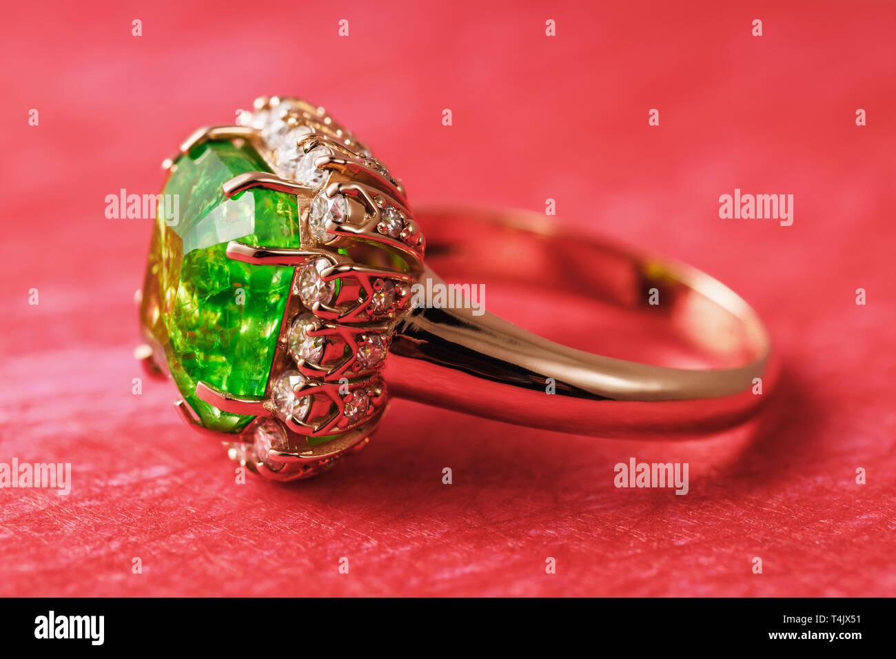 Golden Ring mit einem großen Smaragd und einen Weg der kleinen Cubic Zirkonia rot Abstrakt Hintergrund, Seitenansicht Stockbild