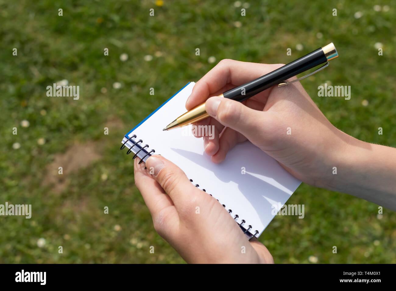 Boy's Hand mit einem gelb-schwarzen Stift über einem offenen Notepad auf dem Hintergrund des grünen Grases und weißen Blumen im Park. Sauberes weißes Blatt. Zu w Stockfoto