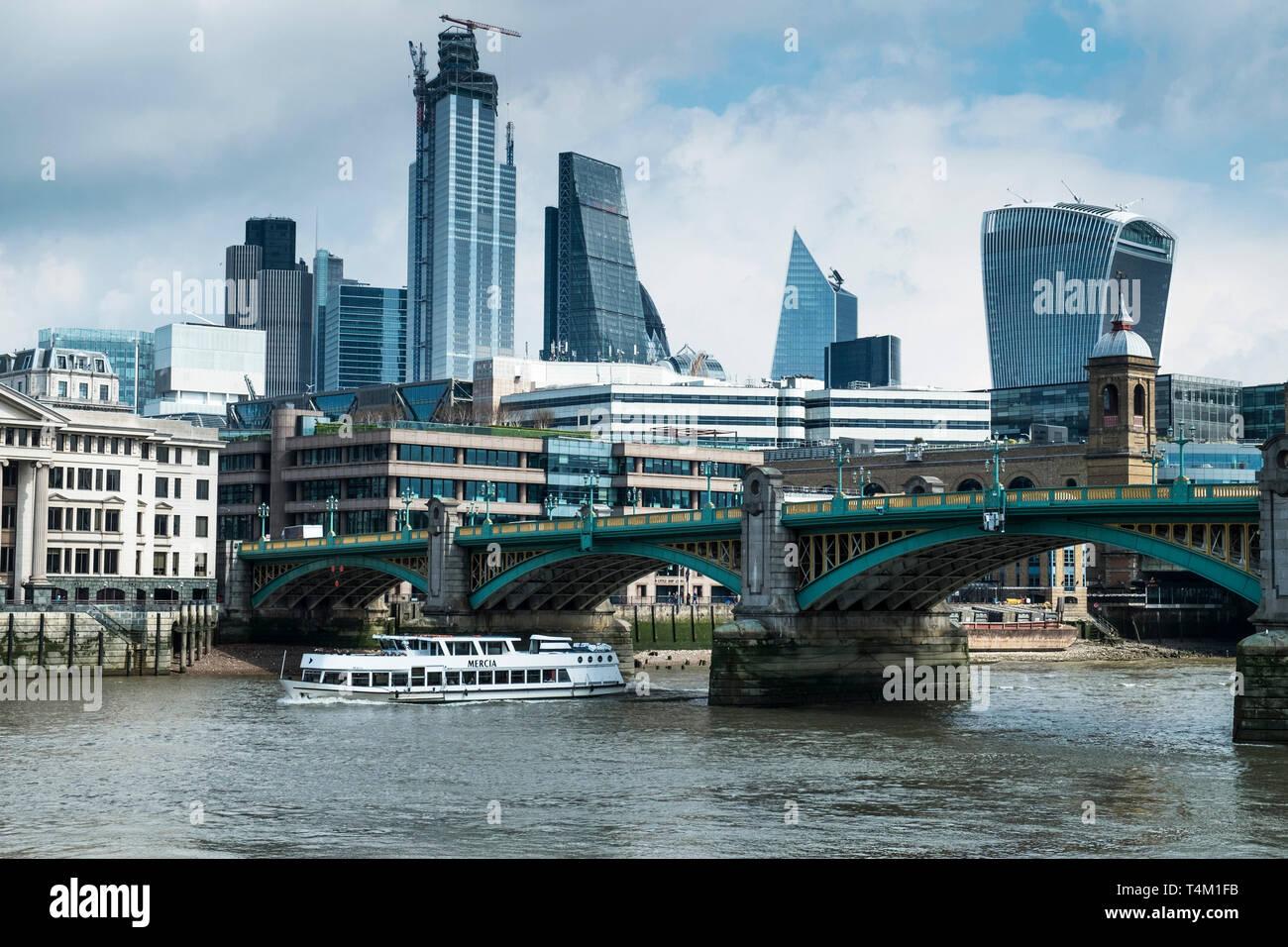 Die touristische Sehenswürdigkeiten boot Mercia vorbei unter die Southwark Bridge über die Themse mit der ikonischen Hochhäusern im Hintergrund. Stockbild