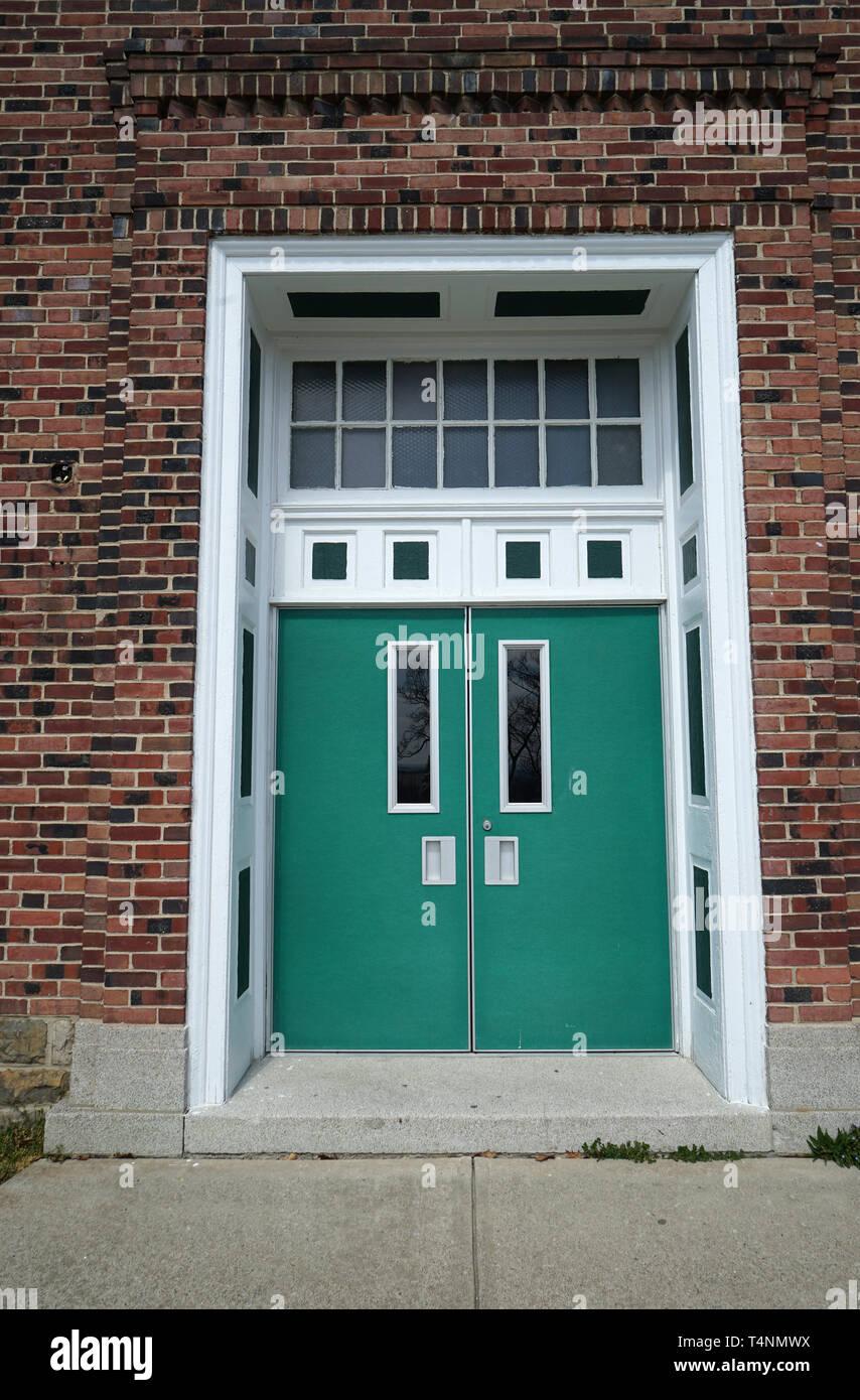Grüne Türen für ein rotes Backsteingebäude. Über den Türen ...