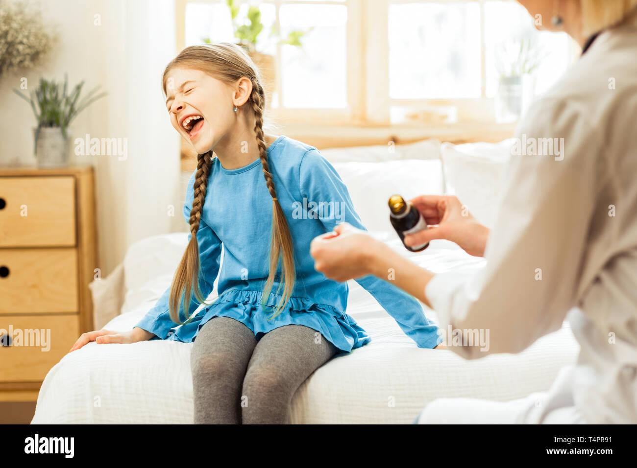 Verweigerung der Medizin zu nehmen. Wenig krank , langhaarige Mädchen im Krankenhaus das Kreischen und die Ablehnung eines Arzneimittels durch einen Arzt in Anspruch zu nehmen Stockbild