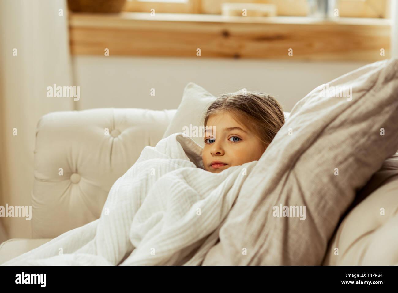 Ein krankes Mädchen im Bett. Kleine süße ziemlich krank braunhaarige Mädchen mit einer Erkältung im Bett lag, eingewickelt in eine warme Decke Stockbild