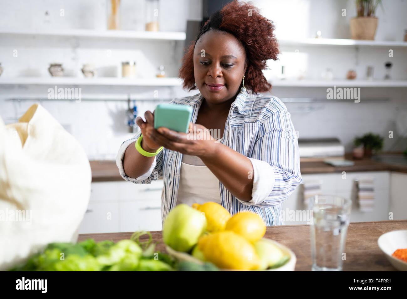 Meine Küche. Freuen lockigen Haaren stehende Frau am Tisch und Gemüse Stockbild