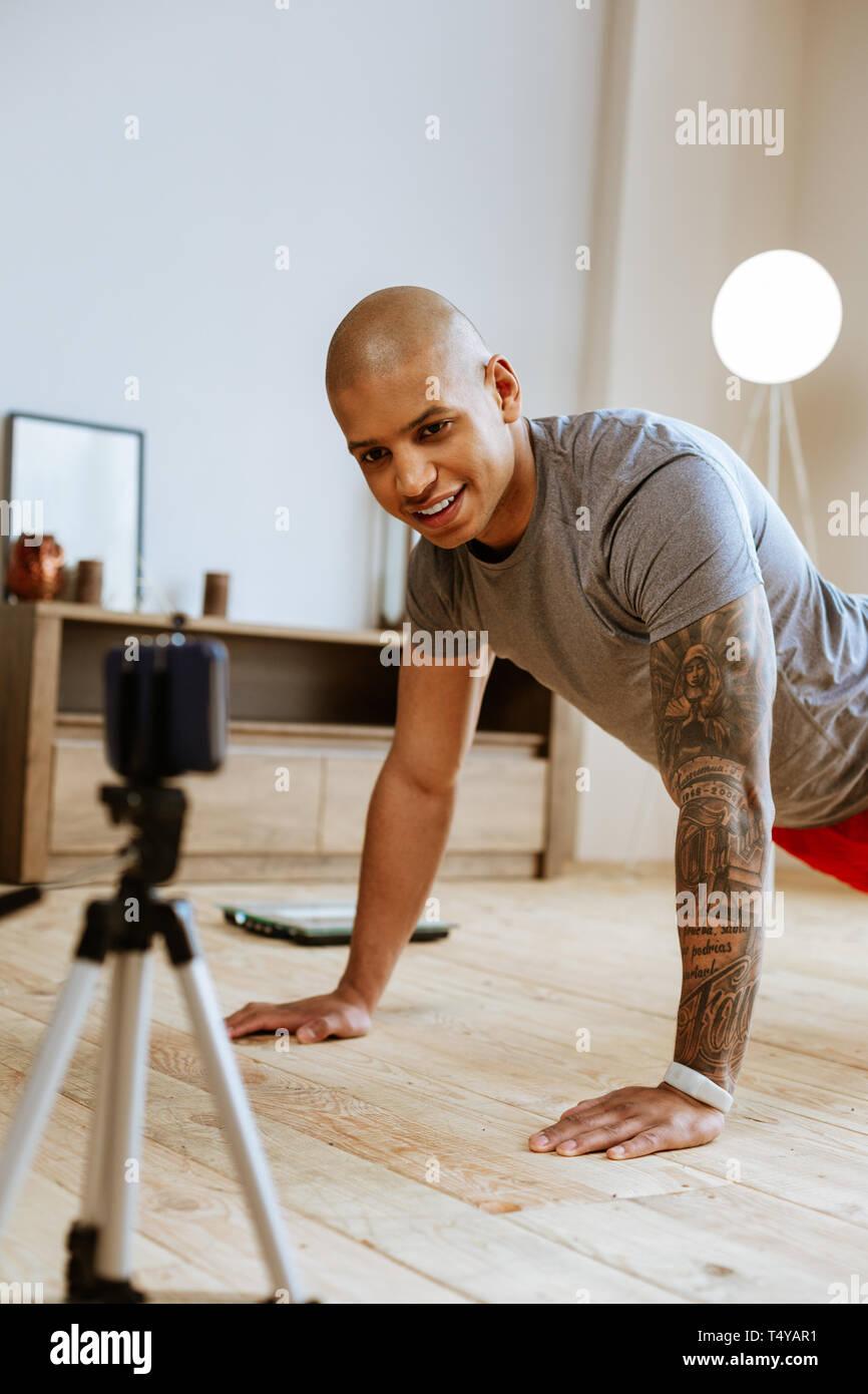 Dunkelhäutige Sportler zeigen Übungen während der Video Stockbild