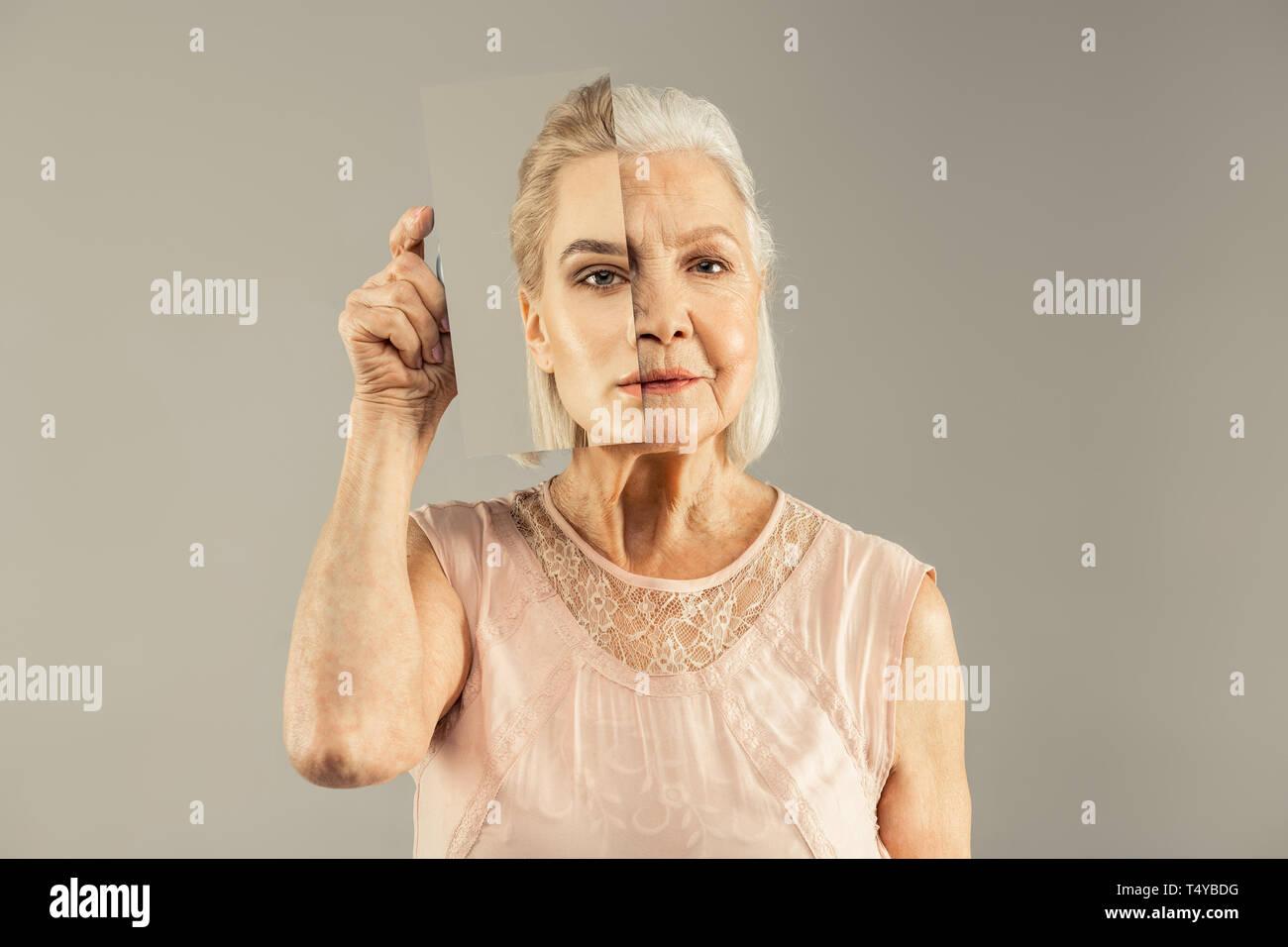 Ernsthafte gealterte Frau mit einem Spiegel in der Nähe von ihr Gesicht Stockbild
