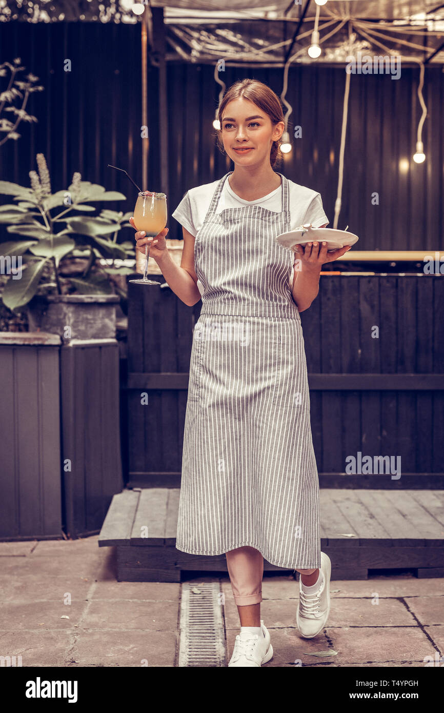 Junge Frau salzen Essen für die Gäste begeistert Stockbild