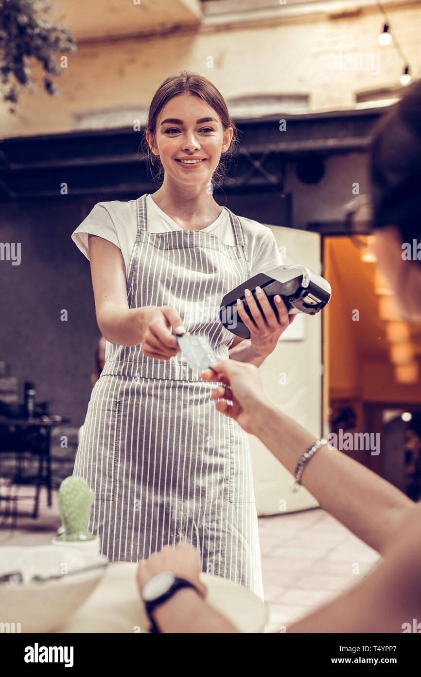 Freudige positive Kellnerin Holding eine Bank Terminal Stockbild