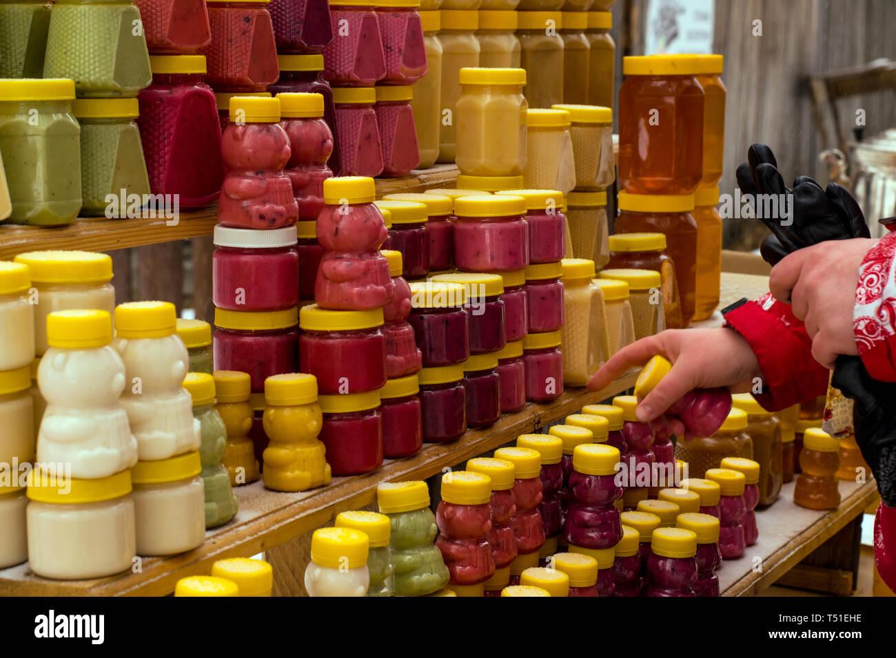 Mädchen mit Handschuhen wählt, Honig und Spezialitäten auf der Theke im Winter Stockfoto