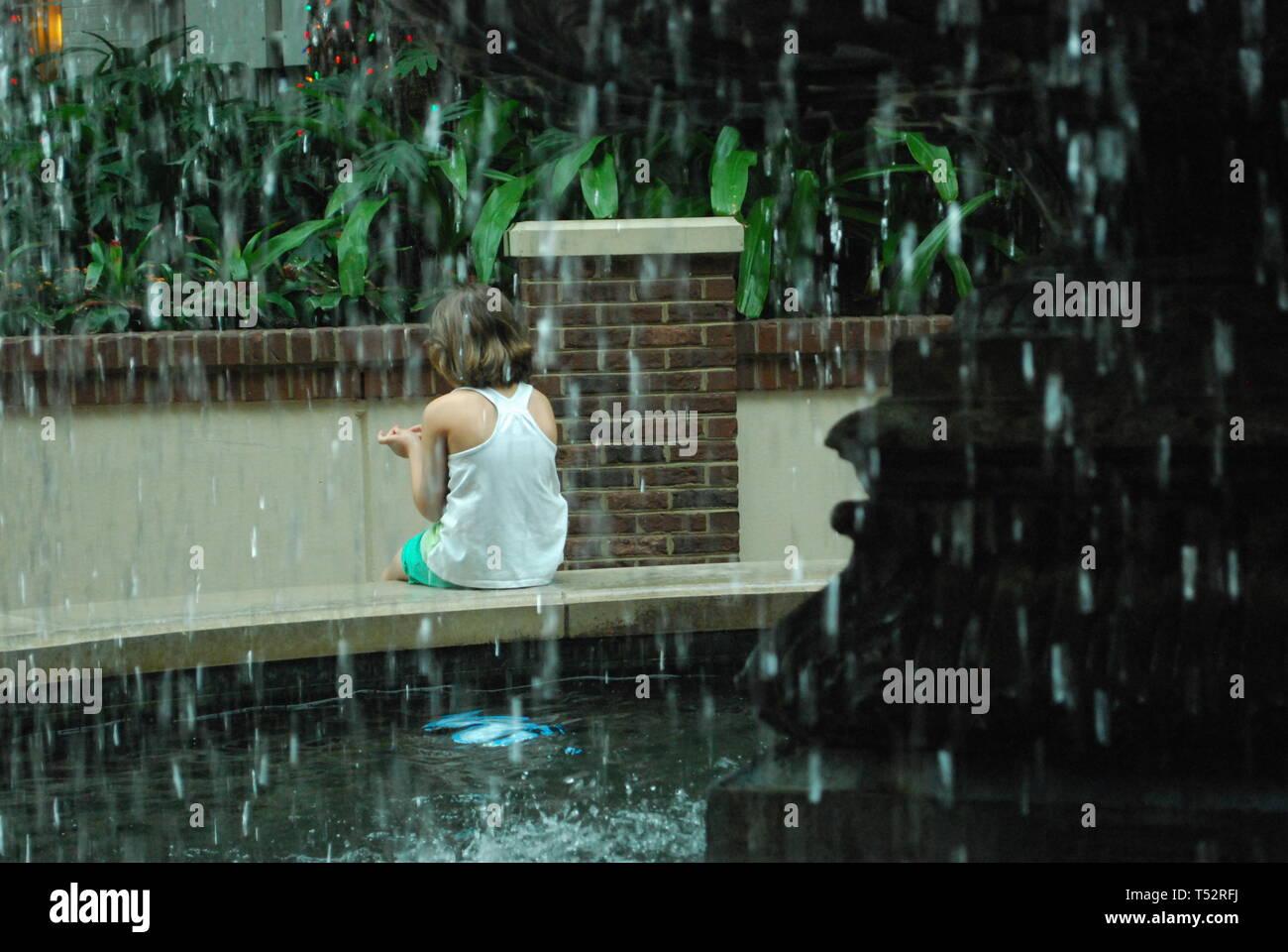 Blick durch Tropfen der Brunnen auf das kleine Mädchen allein in den tropischen Garten. Trauriges Kind wartet auf jemanden. Konzept der Annahme Stockfoto