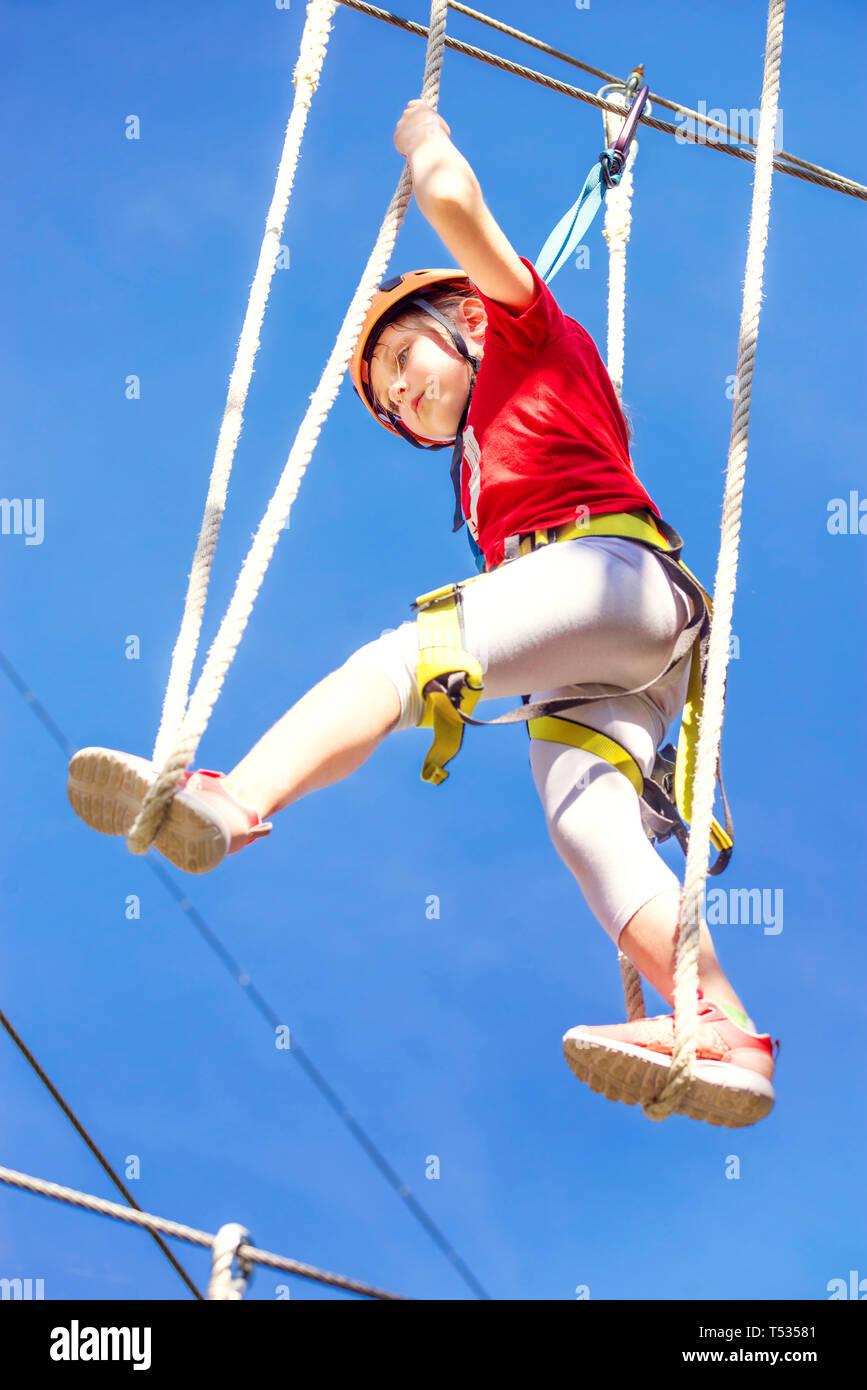 Wenig kaukasische Mädchen an outdoor Baumwipfel klettern Adventure Park brave Stockbild