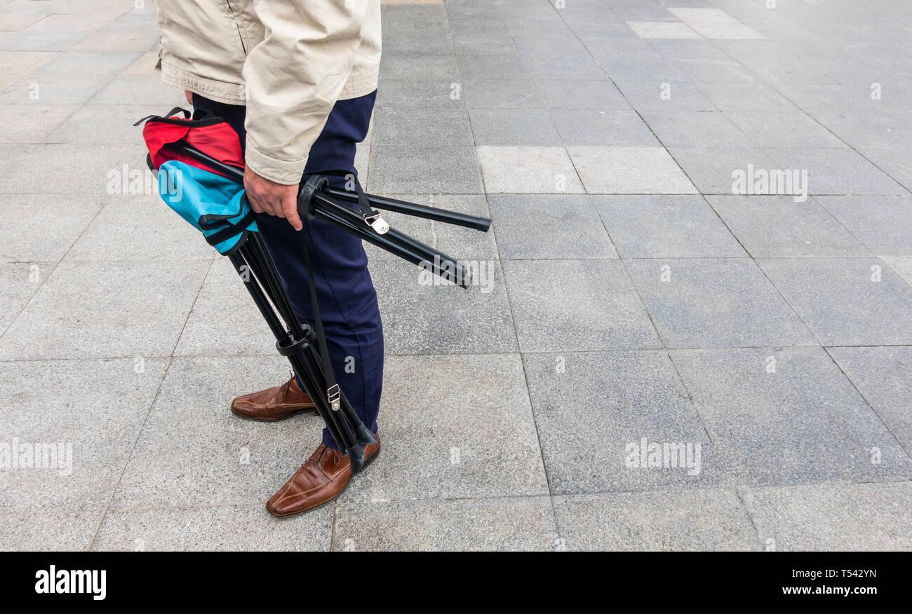 Mann, der zwei portable klappbarer Hocker in Sevilla Stockbild