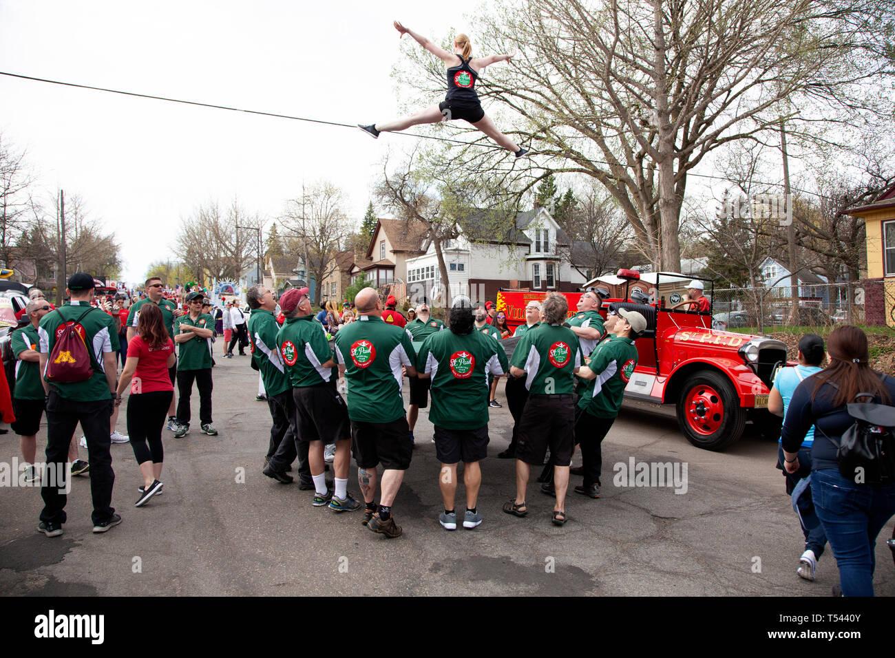 St. Paul Bouncing Team mit Frau in der Luft und Männer mit einem Trampolin im Cinco de Mayo Parade. St. Paul Minnesota MN USA Stockbild