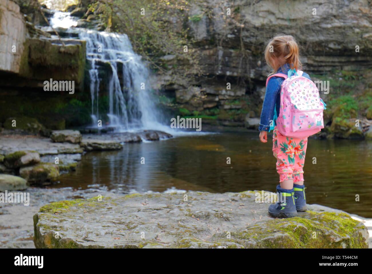 Ein 3 Jahre altes Mädchen Uhren Wasser cascading bei West Burton fällt in den Yorkshire Dales National Park Stockfoto