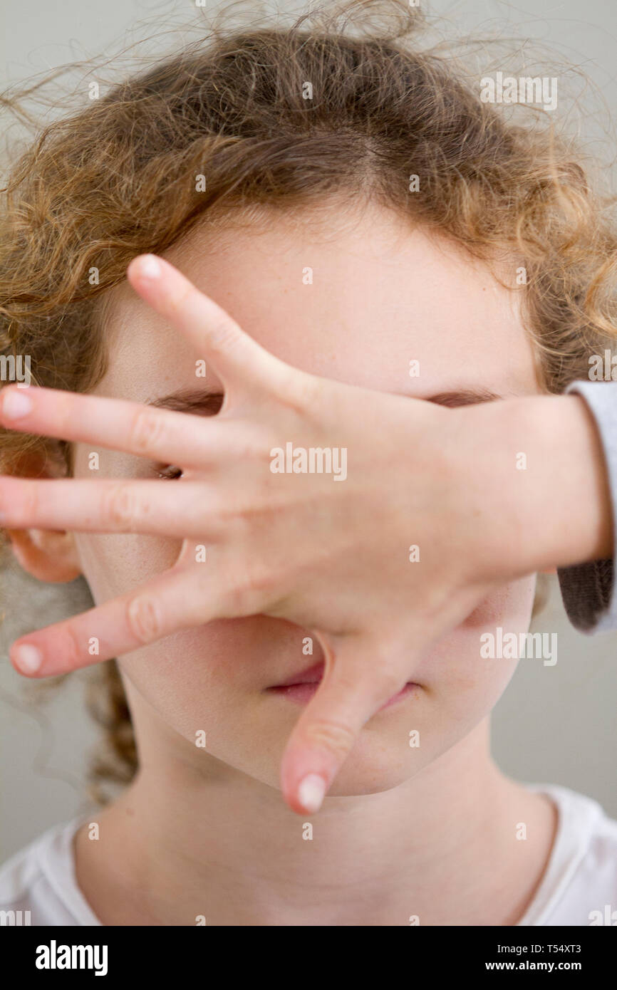 Portrait eines Mädchens mit einer Hand vor ihrem Gesicht Stockbild
