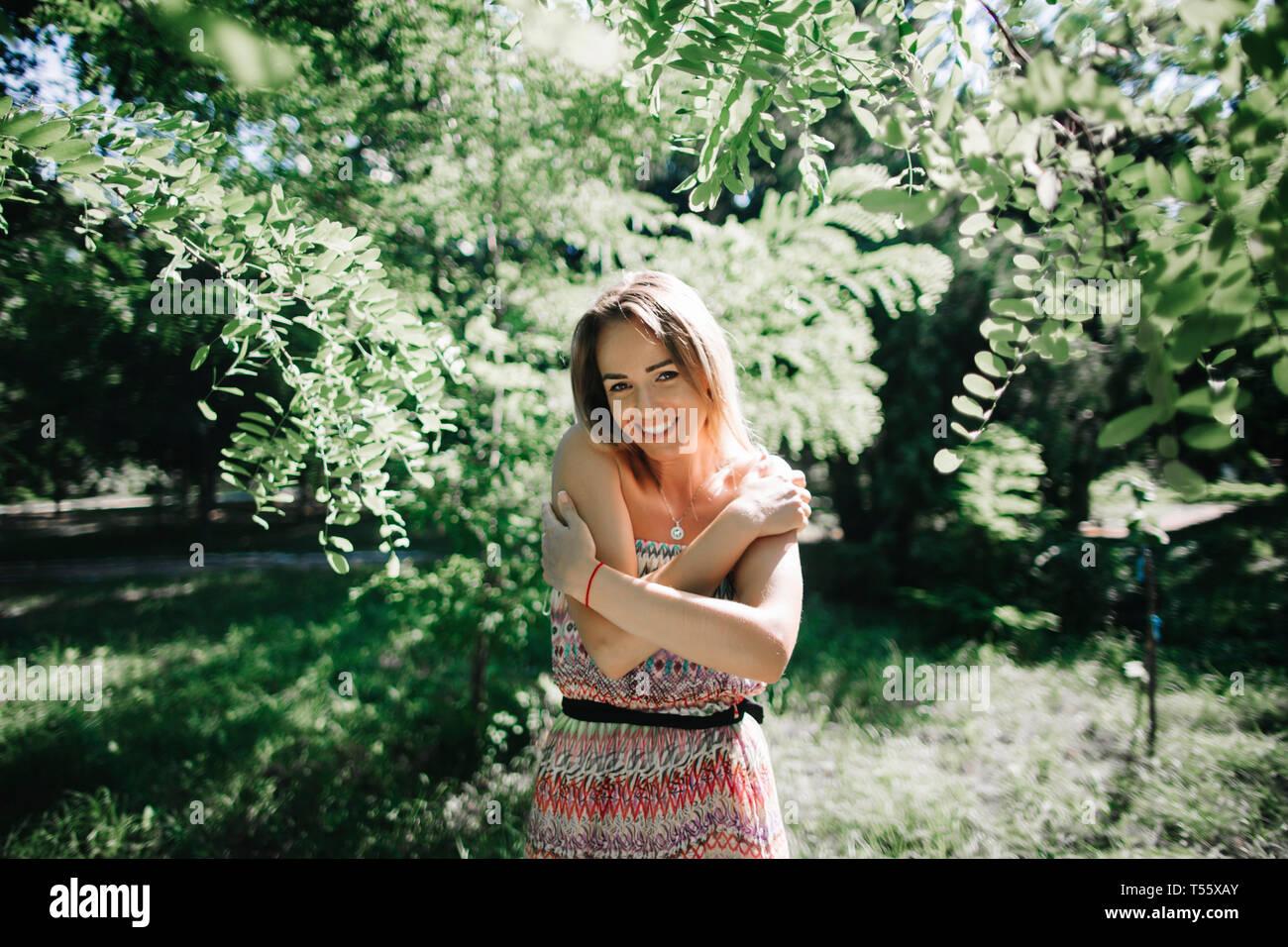 Junge Frau lächelnd in park Stockfoto