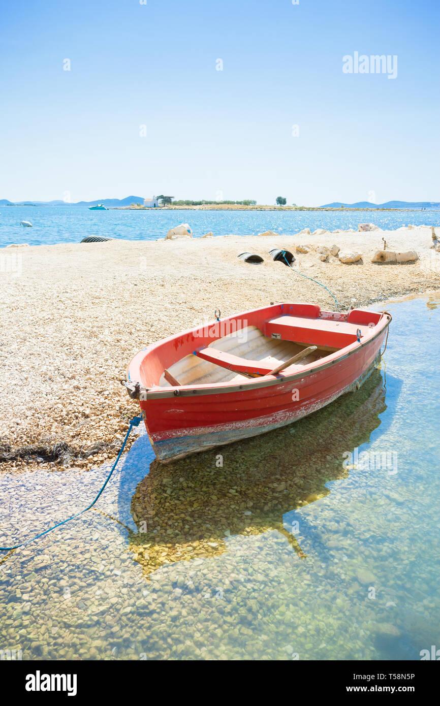 Pakostane, Kroatien, Europa - ein rotes Boot am Strand von Pakostane Stockfoto