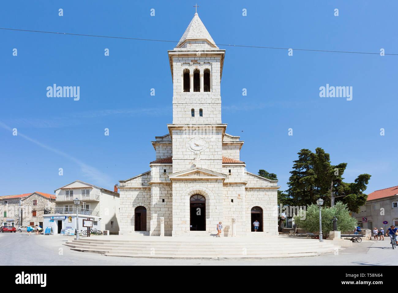 Pakostane, Kroatien, Europa - 27. August 2017 - Touristen zu Fuß rund um den Kirchturm von Pakostane Stockfoto