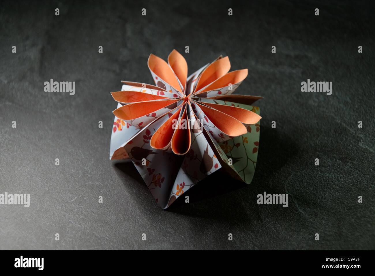 Origami Blume Blüte - Papier Kunst auf strukturierten Hintergrund Stockfoto