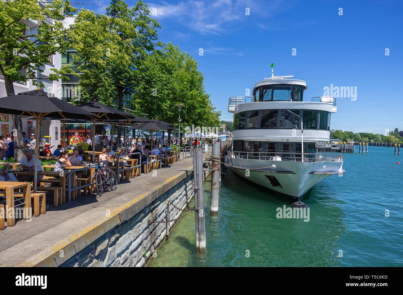 Street Scene mit Restaurant an der Seepromenade mit angedockten Schiff, Friedrichshafen am Bodensee, Baden-Württemberg, Deutschland, Europa. Stockbild