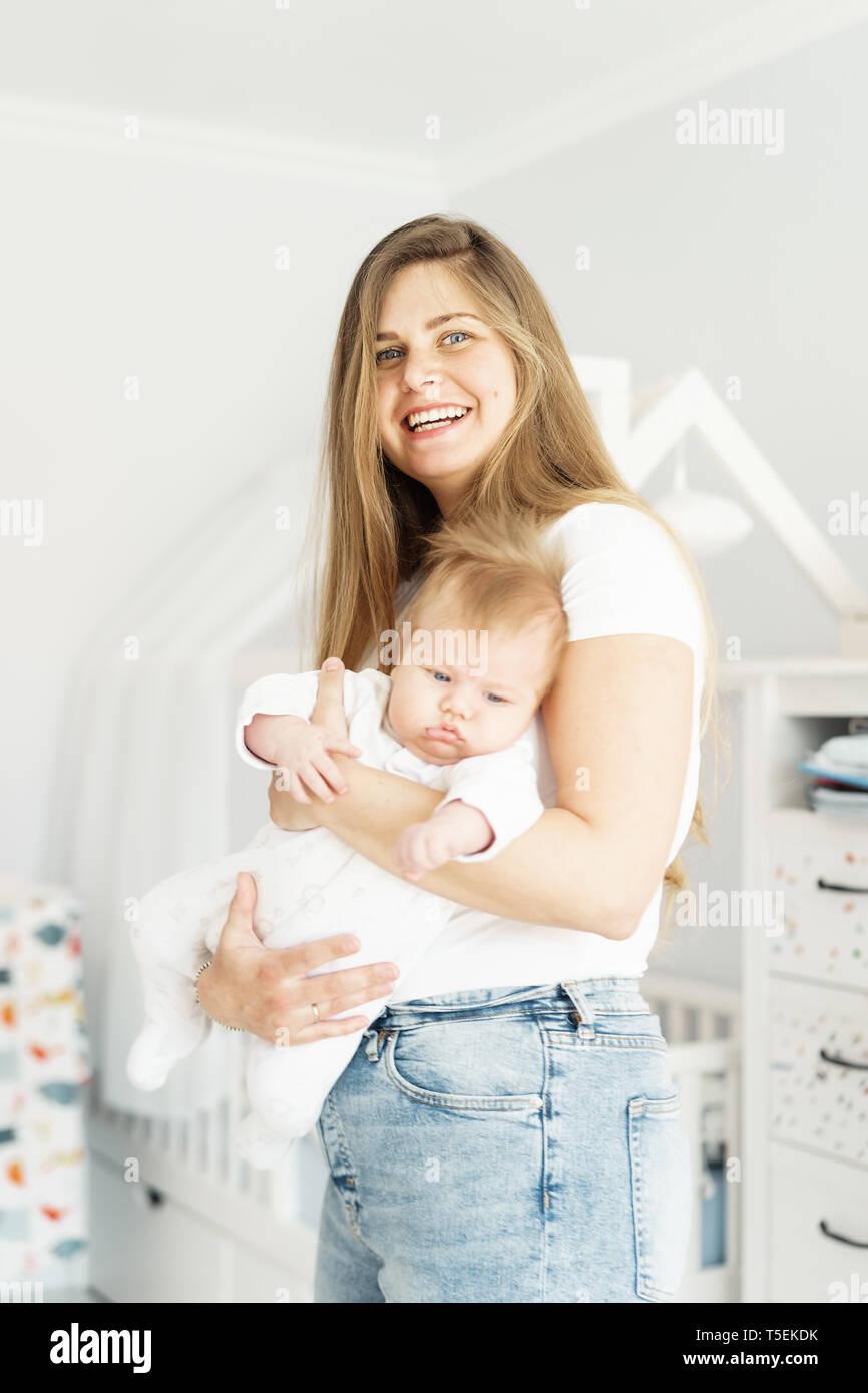 Hübsche Blondine lange heared Mutter und neugeborenen Sohn in ihre Arme in den weißen Kinder Zimmer. Das Konzept des neuen Lebens, der Liebe und der Hilflosigkeit. Stockbild