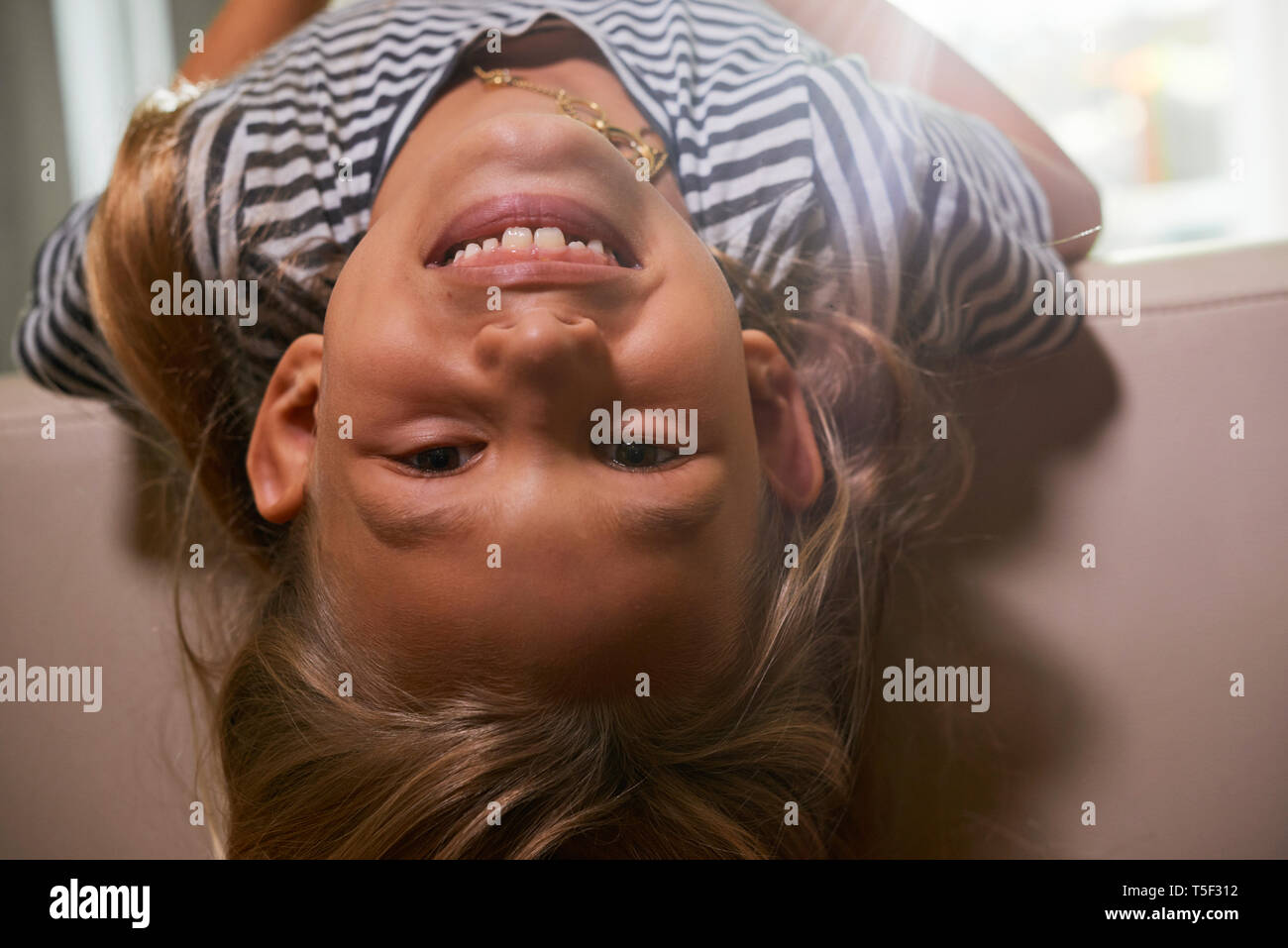 Fröhliches Mädchen ruht auf einem Sofa Stockbild