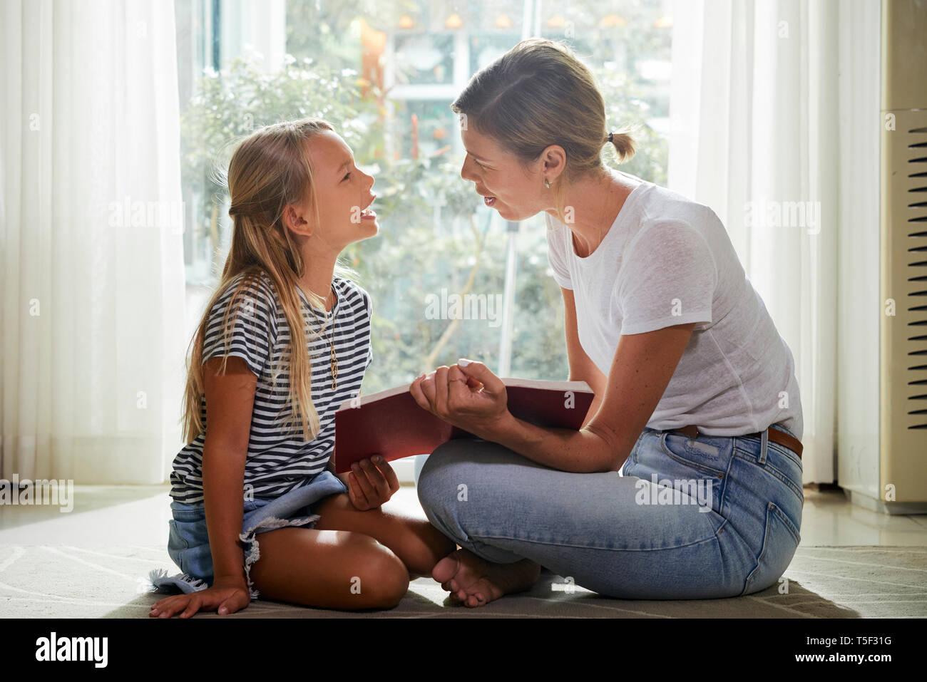 Mutter und Tochter Buch diskutieren Stockbild