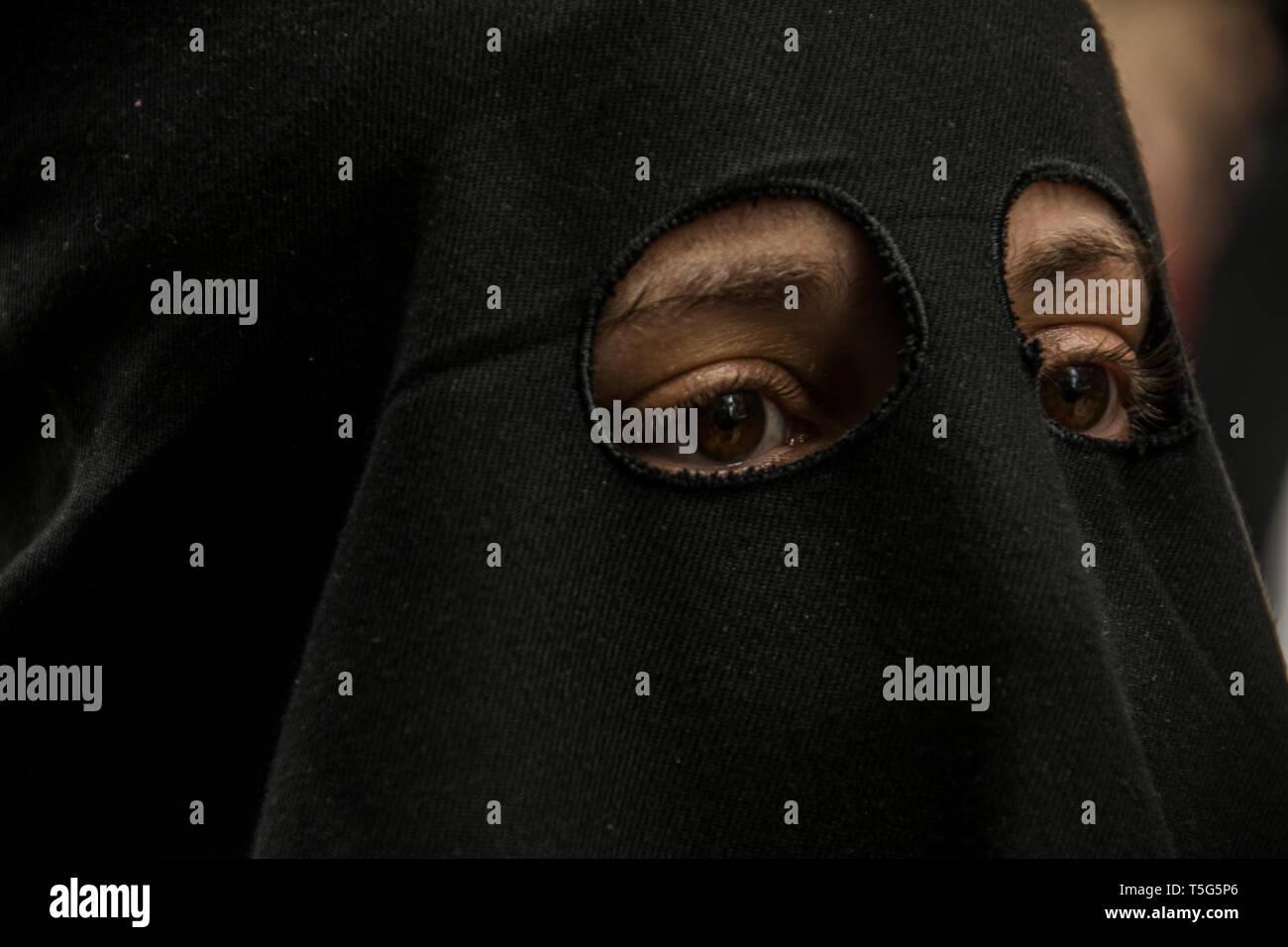 Augen von einer vermummten Frau in der Prozession der Dame der Einsamkeit in Madrid, Spanien. Prozession der Muttergottes von Einsamkeit und Hilflosigkeit, Brot Stockbild