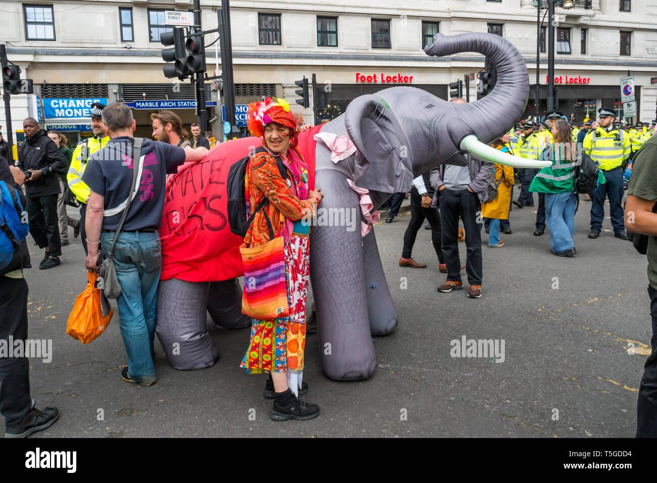 London, Großbritannien. 24. April 2019. Die Leute halten einen aufblasbaren Elefanten bei Marble Arch. Die Polizei wurde entfernen Menschen blockieren Oxford St, die letzte Straße Block um Marble Arch an diesem Nachmittag. Einige Leute wurden auf und werden sorgfältig heraus, die von den Offizieren cut gesperrt, während andere saß ruhig von der Polizei umstellt und wartete, während eine kleine Menge durch mehrere Linien der Polizei beobachtete, wie die Offiziere, die versucht, sie zu erhalten, zu verschieben, verhaftet zu werden. Bei Marble Arch der Protest mit Trommeln und Tanzen, kostenloses Essen und Hunderte von Zelten fortgesetzt. Peter Marshall / alamy Leben Nachrichten Stockbild