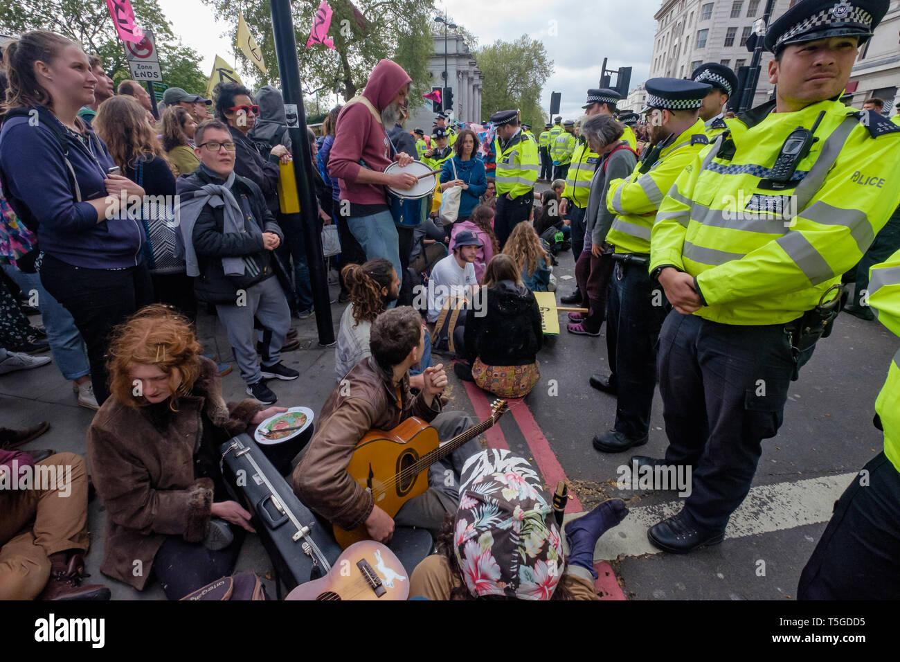 London, Großbritannien. 24. April 2019. Die Polizei wurde entfernen Menschen blockieren Oxford St, die letzte Straße Block um Marble Arch an diesem Nachmittag. Einige Leute wurden auf und werden sorgfältig heraus, die von den Offizieren cut gesperrt, während andere saß ruhig von der Polizei umstellt und wartete, während eine kleine Menge durch mehrere Linien der Polizei beobachtete, wie die Offiziere, die versucht, sie zu erhalten, zu verschieben, verhaftet zu werden. Bei Marble Arch der Protest mit Trommeln und Tanzen, kostenloses Essen und Hunderte von Zelten fortgesetzt. Peter Marshall / alamy Leben Nachrichten Stockbild