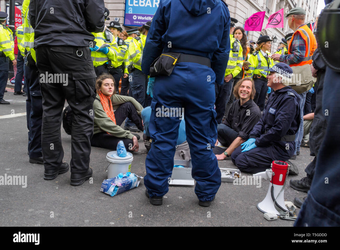 London, Großbritannien. 24. April 2019. Die Polizei wurde entfernen Menschen blockieren Oxford St, die letzte Straße Block um Marble Arch an diesem Nachmittag. Einige Leute wurden auf und werden sorgfältig heraus, die von den Offizieren cut gesperrt, während andere saß ruhig von der Polizei umstellt und wartete, während eine kleine Menge durch mehrere Linien der Polizei beobachtete, wie die Offiziere, die versucht, sie zu erhalten, zu verschieben, verhaftet zu werden. Bei Marble Arch der Protest mit Trommeln und Tanzen, kostenloses Essen und Hunderte von Zelten fortgesetzt. Peter Marshall / alamy Leben Nachrichten Stockfoto