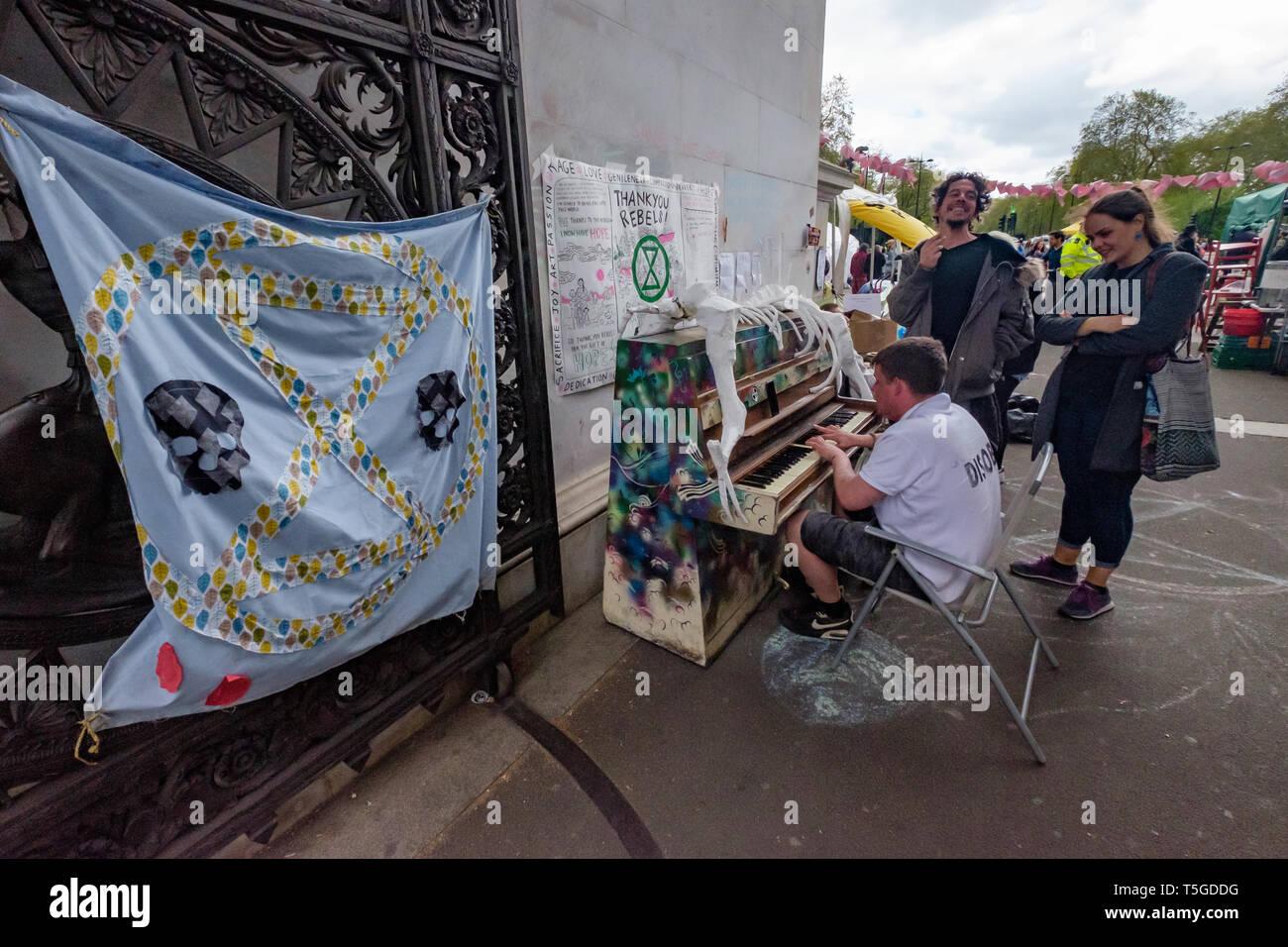 London, Großbritannien. 24. April 2019. Ein Mann spielt ein Klavier unter Marble Arch und die Menschen zu beobachten. Die Polizei wurde entfernen Menschen blockieren Oxford St, die letzte Straße Block um Marble Arch an diesem Nachmittag. Einige Leute wurden auf und werden sorgfältig heraus, die von den Offizieren cut gesperrt, während andere saß ruhig von der Polizei umstellt und wartete, während eine kleine Menge durch mehrere Linien der Polizei beobachtete, wie die Offiziere, die versucht, sie zu erhalten, zu verschieben, verhaftet zu werden. Bei Marble Arch der Protest mit Trommeln und Tanzen, kostenloses Essen und Hunderte von Zelten fortgesetzt. Peter Marshall / alamy Leben Nachrichten Stockbild