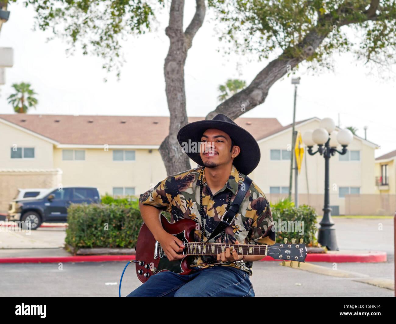 Ein hübscher junger Mann mit dunklen Teint in einem schwarzen, breitkrempiger Hut spielt eine E-Gitarre an der Corpus Christi Southside Farmers' Market. Stockbild