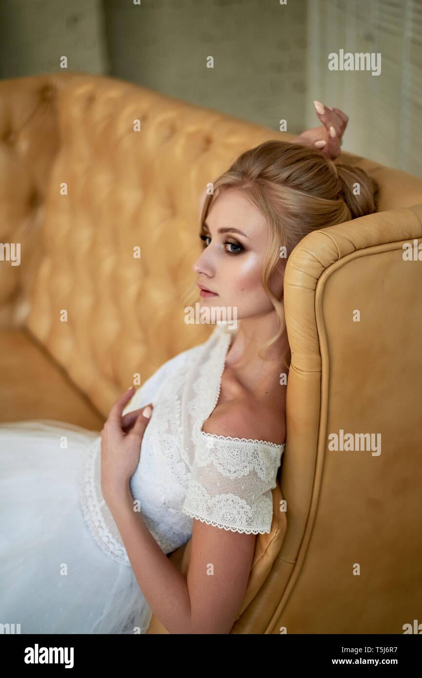 Eine schöne zierliche Blondine sitzt auf der Couch. Die Braut in einem Spitzen Kleid.'s Braut morgen Stockfoto