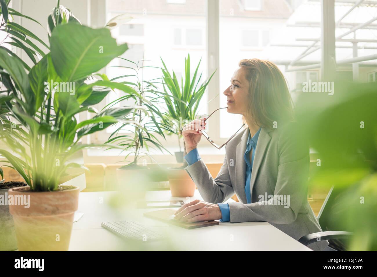 Reife Geschäftsfrau, die in nachhaltige Büro, mit Pflanzen auf Ihrem Schreibtisch Stockbild