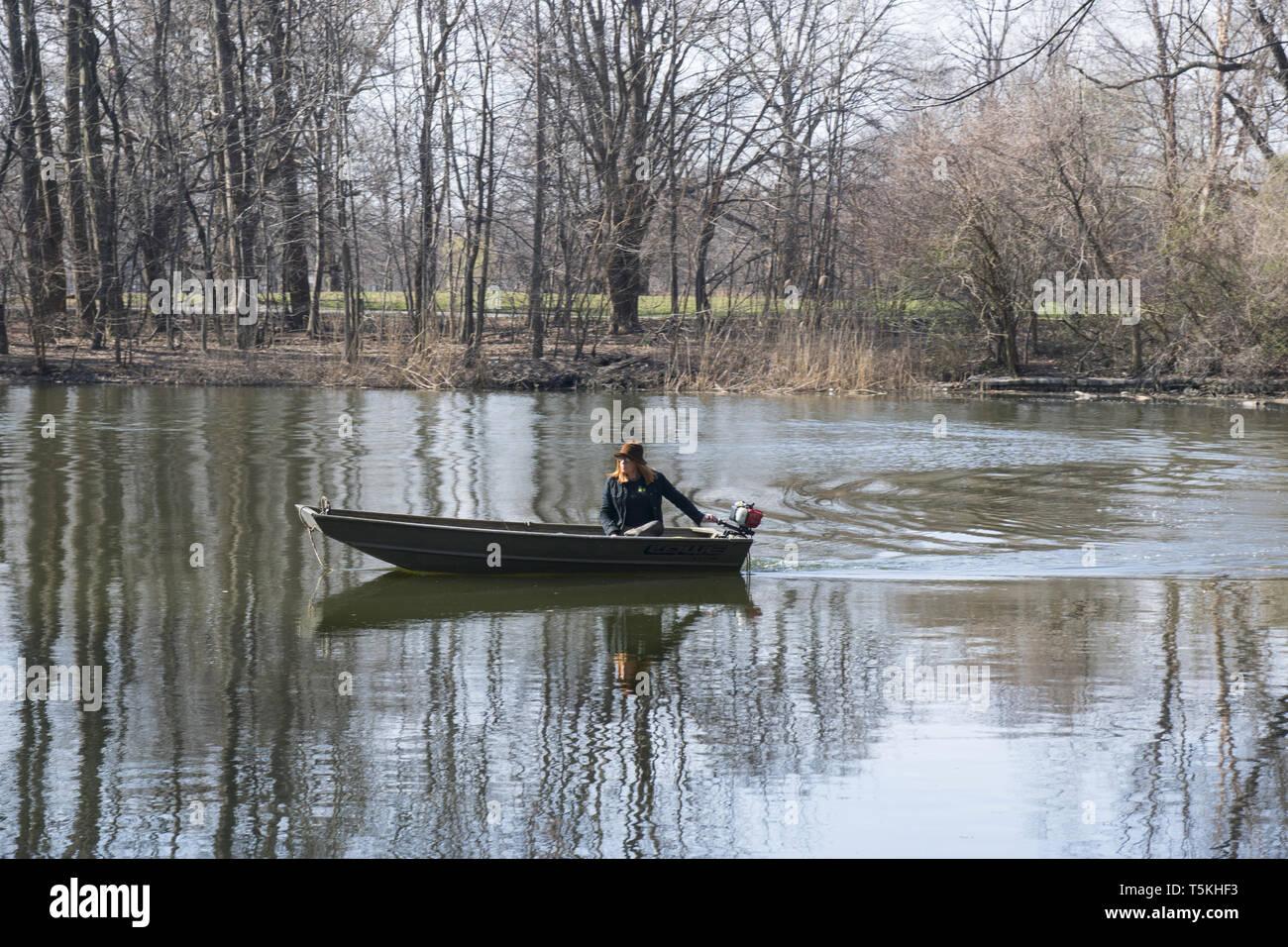Park Arbeitnehmer in einem motorisierten Boot überprüft die See Umwelt in Prospect Park, Brooklyn, New York. Stockbild