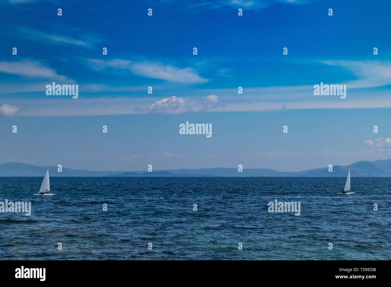 Regatta. Kleine optimist Boote mit weiße Segel, blauer Himmel und Meer, Ägäis, Griechenland Stockbild