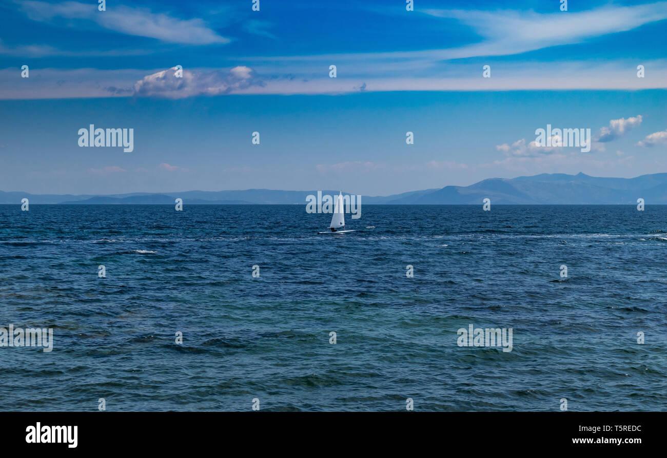 Segeln in der Ägäis, Griechenland. Kleine optimist Boot mit weiße Segel, blauer Himmel und Meer Hintergrund Stockbild