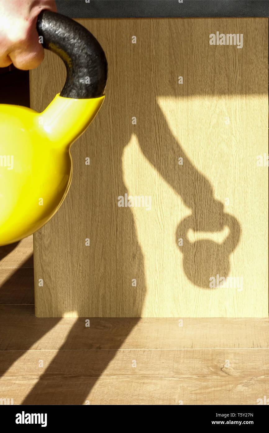 Ein männlicher Arbeiten zu Hause mit einer KETTLEBELL. Die Sonne ist hinter ihm wie ein Schatten. Kettlebells sind eine beliebte Home Gym Option für Krafttraining Stockbild