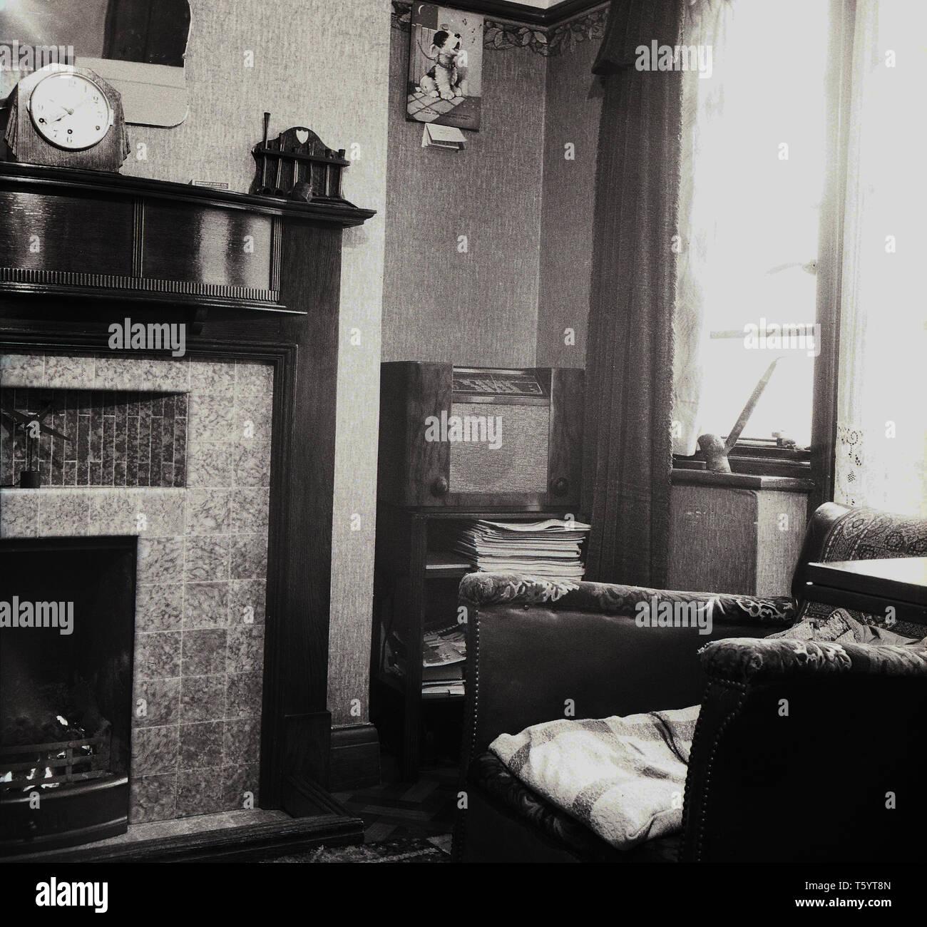 1940 s, historischen, traditionellen Wohnzimmer mit Kamin und Mantel Stück, die mit der drahtlosen Receiver oder Radio set steht in der Ecke, England, UK. Stockbild