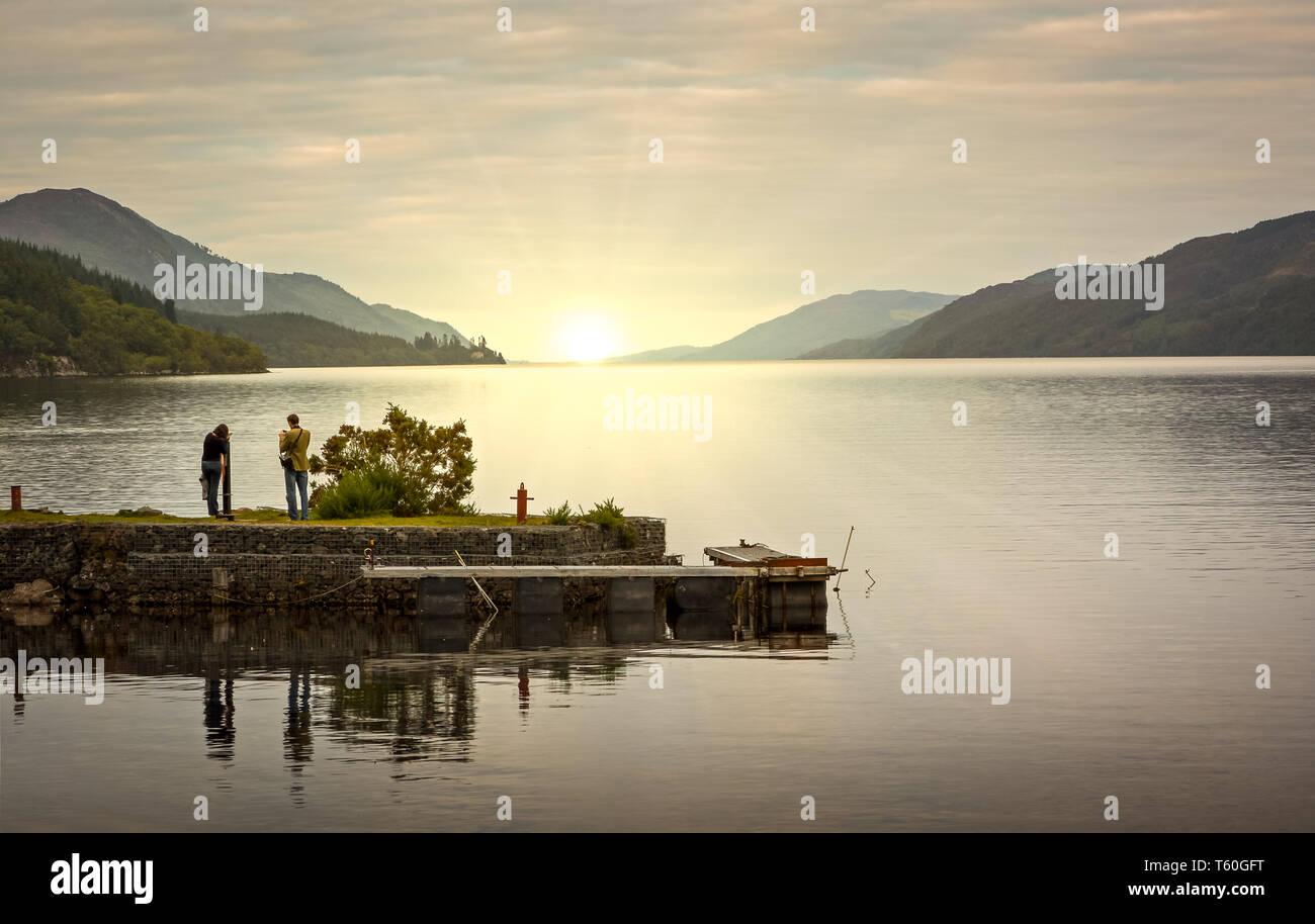 Loch Ness Sonnenaufgang von Fort Augustus fotografiert als junges Paar zum richtigen Zeitpunkt offensichtlich die gleichen atemberaubenden Blick zu schätzen. Stockbild