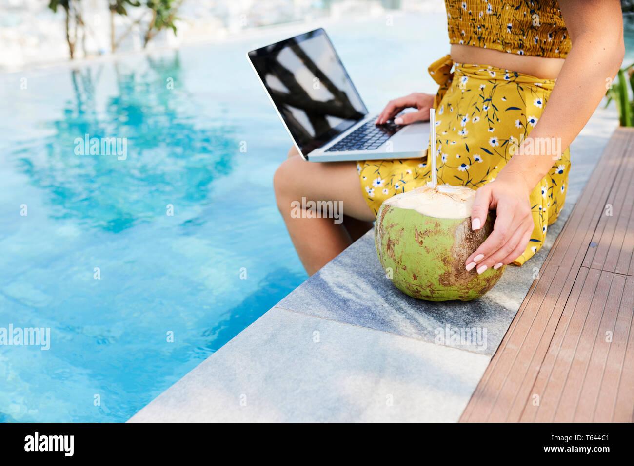 Frau genießen coconut Cocktail bei der Arbeit Stockbild