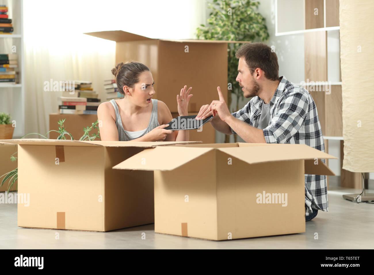 Ehe Umzug kämpfen für eine Tablette sitzen auf dem Boden Stockfoto