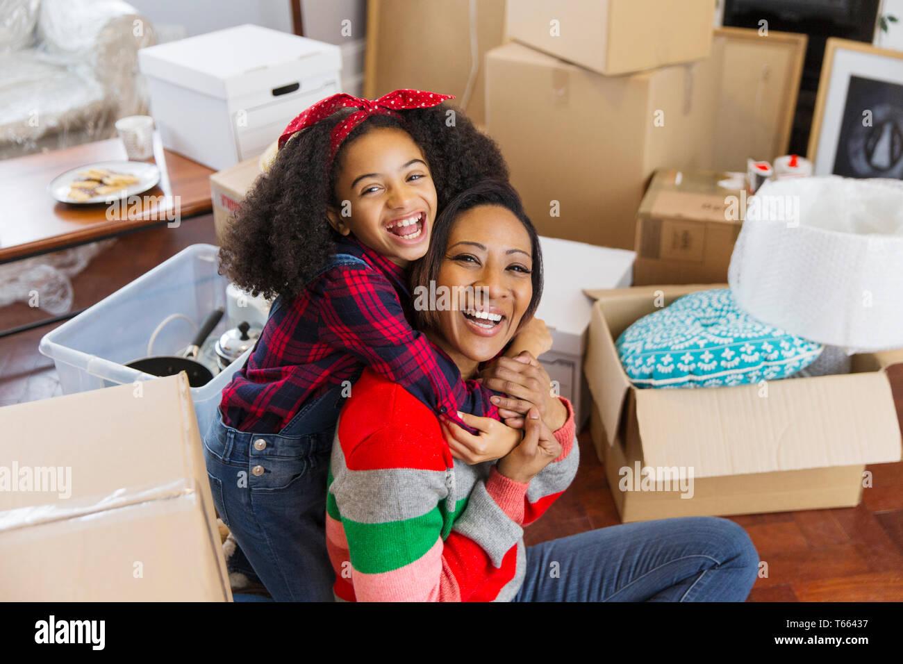 Portrait über glückliche, begeisterte Mutter und Tochter umarmen unter Kartons, Umzug Stockfoto