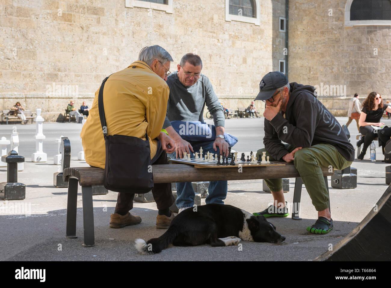 Menschen spielen Schach, Blick auf Männer im mittleren Alter spielen eine Partie Schach in der kapitelplatz in Salzburg, Österreich. Stockbild